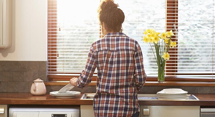 Woman washing up crockery in kitchen.