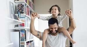 Happy father carrying girl on shoulder while standing at home