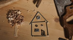 Work tools surrounding a house made of nails and tree made of wood shavings